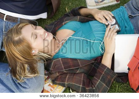 Female student lying on lap of male friend while listening music