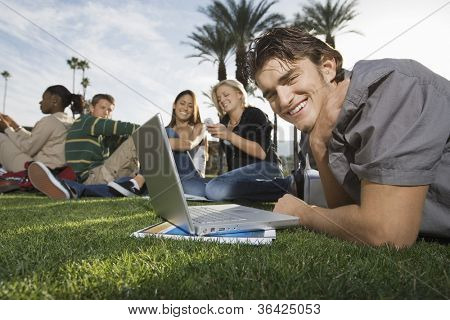 Portrait of a young man using laptop while lying on grass