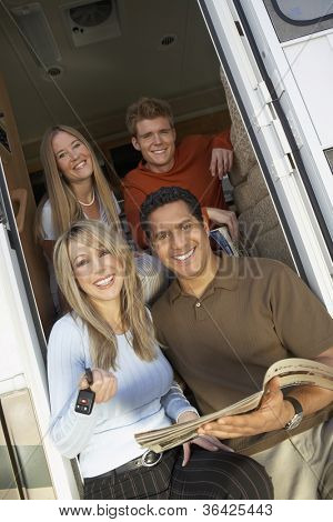 Portrait of happy couple sitting at the doorway of RV