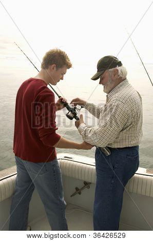 Senior man with grandson fishing on yacht