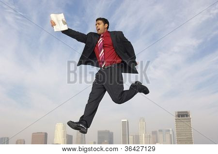 Mixed race businessman running in midair with newspaper
