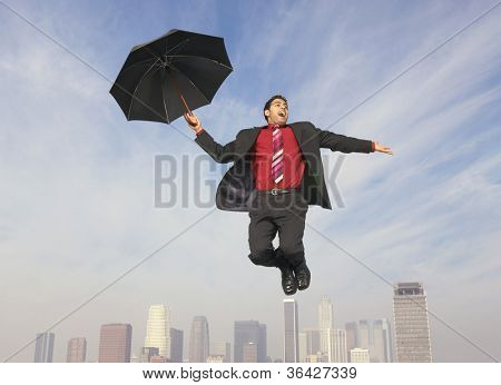 Full length of an ecstatic businessman with an umbrella in midair