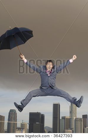 Ecstatic businessman jumping in midair with an umbrella