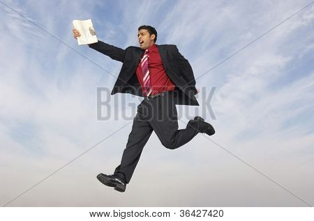 Full length of a mixed race businessman running with newspaper in midair