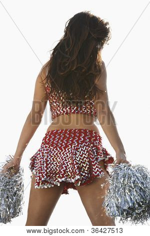 Rear view of a cheerleader holding pompoms