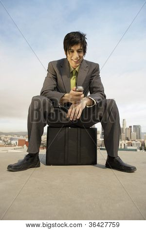 Businessman using cell phone while sitting on briefcase