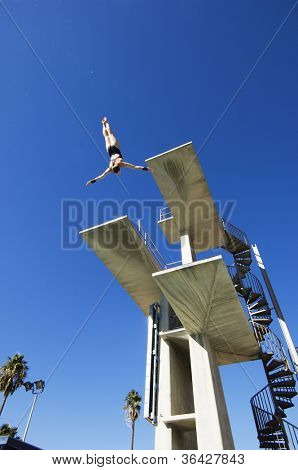 Low angle view of a female diver diving in midair from the springboard