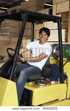 Happy young man driving forklift