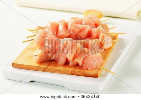 Five meat skewers on a kitchen board with an ecru napkin
