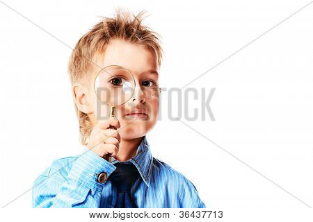 Curious little boy in spectacles is looking through a magnifying glass. Isolated over white background.