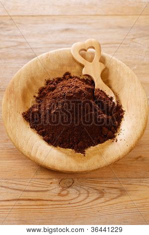 ground coffee powder in wooden plate with heart shape spoon, shallow dof