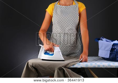 Closeup of a woman ironing clothes. Horizontal format over light to dark gray background. Woman is unrecognizable.
