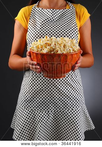 Closeup of a homemaker in an apron holding a bowl of popcorn. Vertical format over a light to dark background. Woman is unrecognizable. Shallow depth of field.