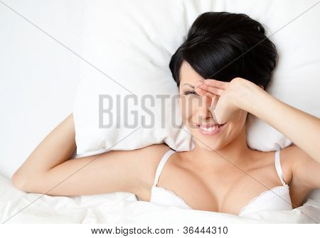 Sleeping sexy woman in the bed with white bedclothes, white background