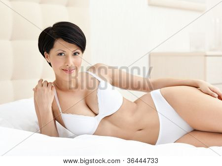 Woman in white perfect bra is lying in the soft bed with white bedclothes
