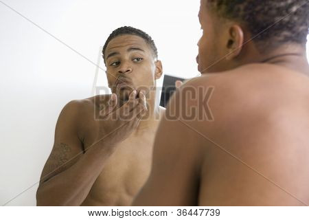 Young African American man examining himself in bathroom mirror