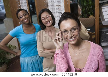 Portrait of cheerful female friends trying on glasses at optometrist