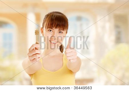 Picture of happy woman with keys showing thumbs-up