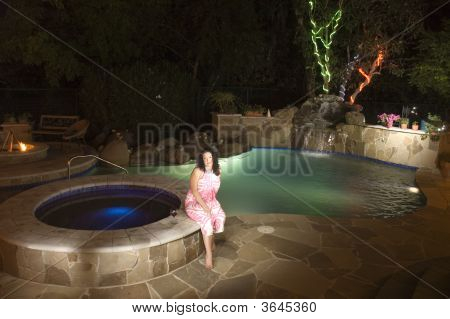 Woman Sitting By Pool At Night