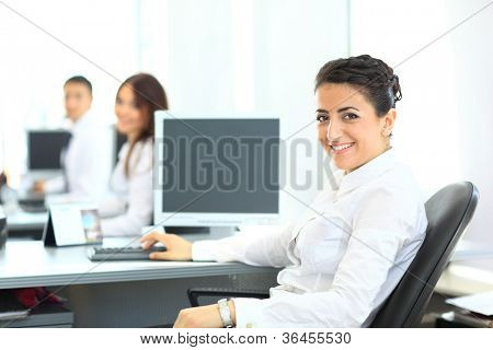 Closeup portrait of business woman giving you cute smile with colleagues in background