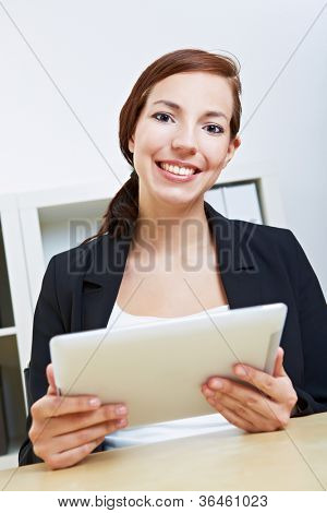 Smiling businesswoman sitting with her tablet pc in an office