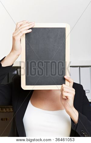 Empty chalkboard in front of face of business woman in her office