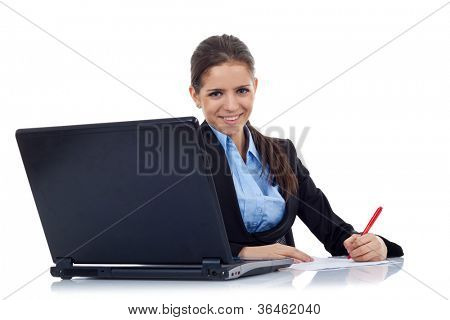 Portrait of an adorable young business woman working at her desk with a laptop and paperwork. Isolated on white