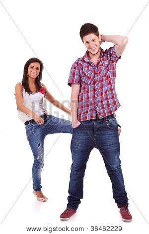 Couple having fun. Young woman kicking her boyfriend in the behind