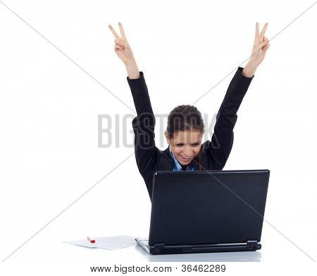 Portrait of a young business woman victorious behind laptop. isolated on white