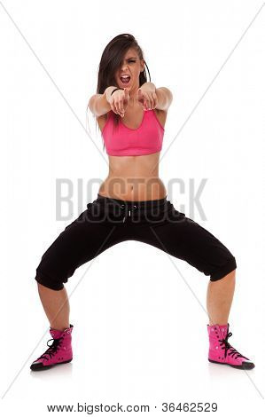 Perky young dancer pointing with both her fingers at you, against white background