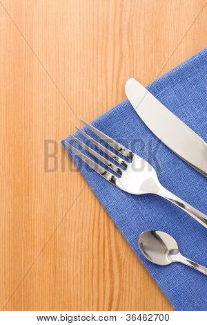 silver fork and knife as utensils on napkin at wooden background