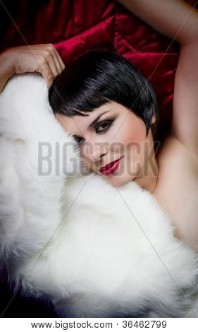 seminude beautiful short haired brunette woman lying on red silk with white fur, old hollywood star style