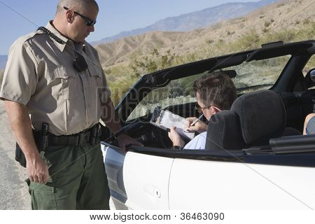 Middle aged man writing on ticket with traffic officer standing by car