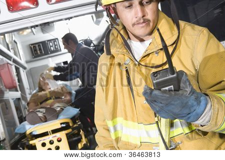 Fire worker holding walkie-talkie with patient and EMT doctor in the background