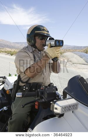 Police officer on motorbike monitoring speed though radar gun