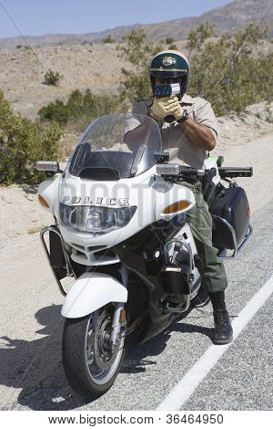 Full length of a police officer on motorbike monitoring speed though radar gun