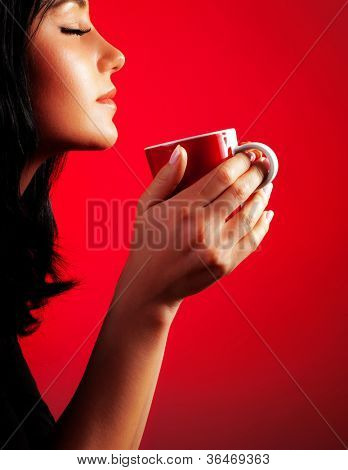 Beautiful lady drinking coffee, brunette enjoy cup of hot chocolate, side view cute girl isolated on red background, portrait of female with morning tea, gorgeous woman holding cappuccino mug