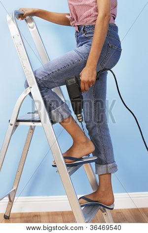 Low section of a woman with driller climbing ladder
