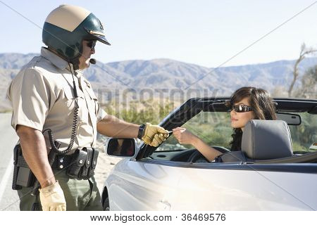 Mature police man checking woman's license