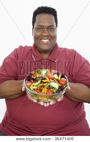 Portrait of happy African American man with a bowl of salad isolated over white background