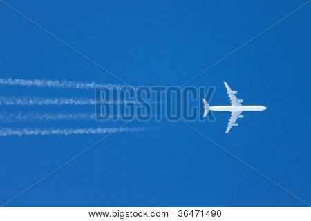 Airplane with contrails in a clear blue sky