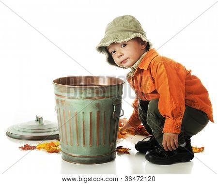 An adorable preschooler picking up colorful leaves to put in a small trash can.  On a white background.