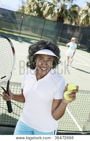 Senior woman holding tennis racquet and ball against sky