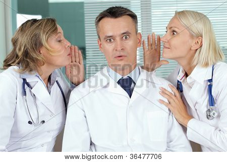 Portrait of surprised male clinician between two gossiping women