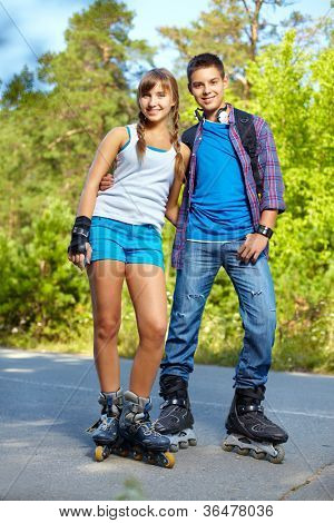 Couple of happy teens on roller skates looking at camera outside