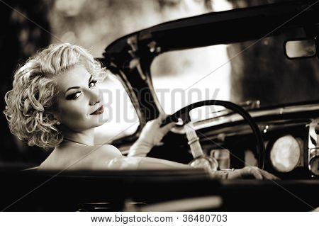 Retro woman behind steering wheel