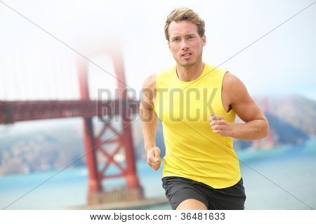 Running in San Francisco. Athlete runner working out jogging by Golden Gate Bridge, San Francisco, USA. Young fit caucasian sport fitness model.