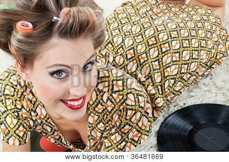 High angle view of beautiful young woman in hair curlers lying on rug beside vinyl records