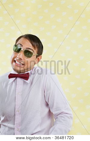 Portrait of funny male geek making a face over yellow wallpaper