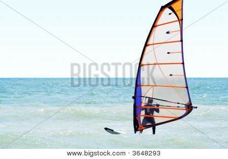 Silhouette Of A Windsurfer On The Sea In The Afternoon